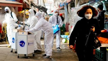 A woman wearing a mask to prevent contracting the coronavirus reacts as employees from a disinfection service company sanitize a traditional market in Seoul