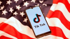 Tik Tok logo is displayed on the smartphone while standing on the U.S. flag in this illustration