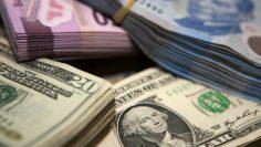 Stacks of Mexican pesos and U.S. dollar bills